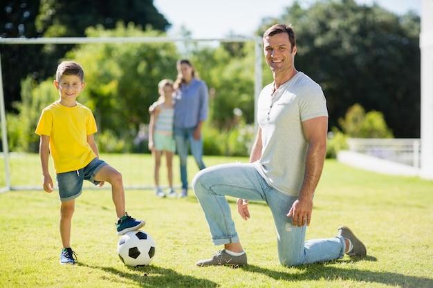 Vater und sohn spielen fußball im park an einem sonnigen tag