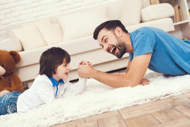 Vater und sohn spielen im armdrücken.
