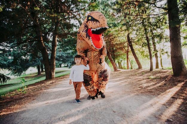 Vater und sohn spielen im park mit einem dinosaurierkostüm und haben spaß mit der familie im freien
