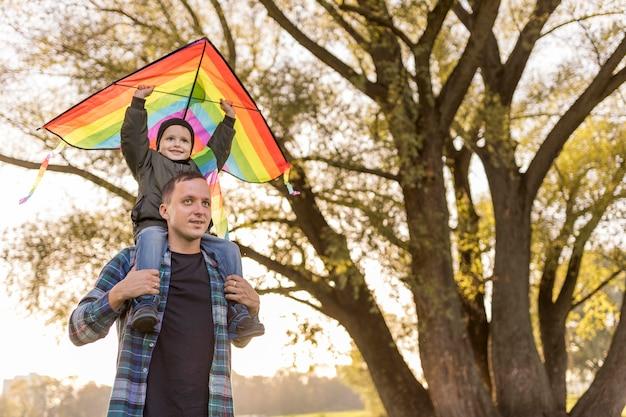 Vater und sohn spielen mit einem drachen