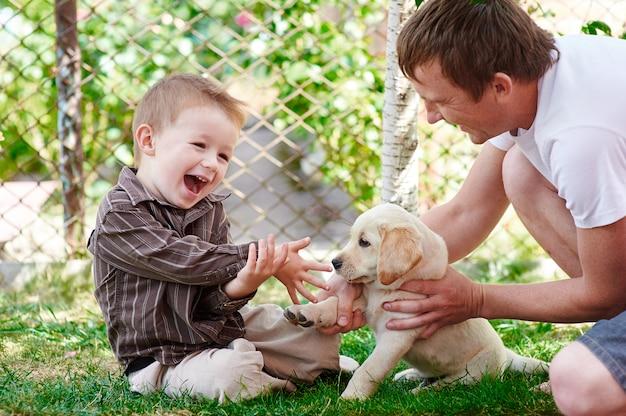 Vater und sohn spielen mit einem labrador-welpen im garten