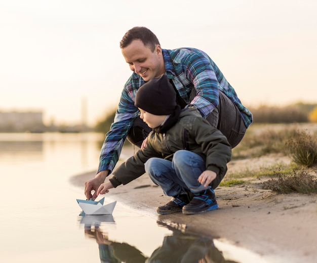Vater und sohn spielen mit einem origami-boot