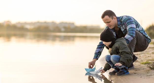 Vater und sohn spielen mit einem papierboot