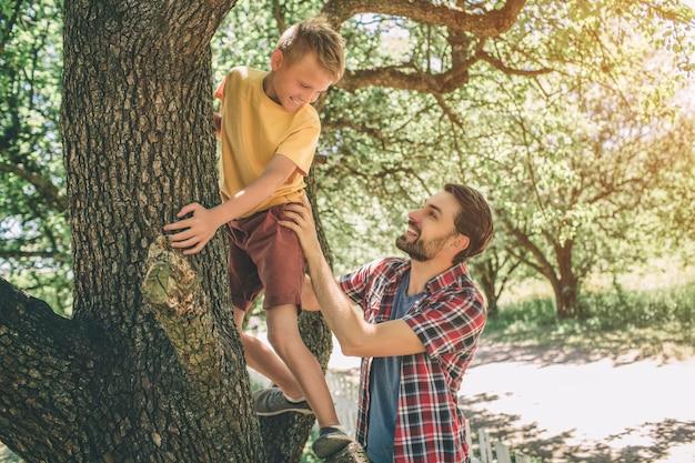 Vater und sohn spielen miteinander. guy unterstützt sein kind. junge schaut auf vater herab. sie lächeln. beide sind glücklich