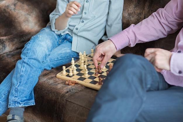 Vater und sohn spielen schach, während sie zu hause zeit miteinander verbringen