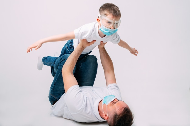 Vater und sohn spielen während der quarantäne in medizinischen masken.
