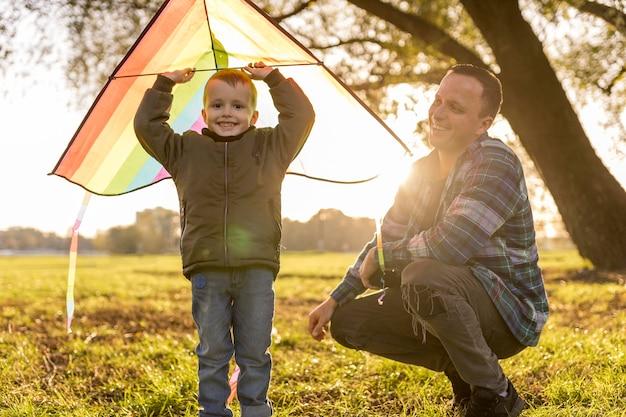 Vater und sohn spielen zusammen mit einem bunten drachen