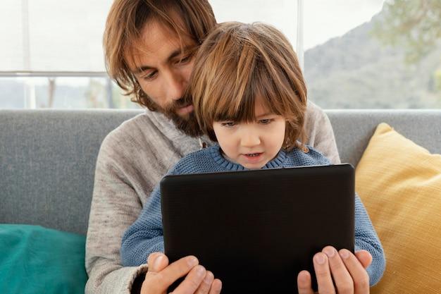 Vater und sohn spielen zusammen mit tablette