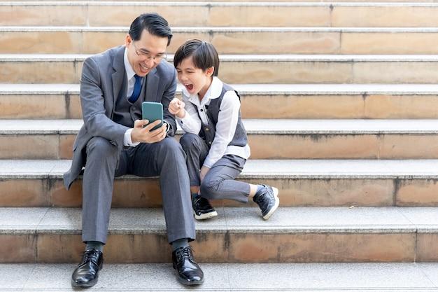 Vater und sohn spielen zusammen smartphone auf geschäftsviertel urban