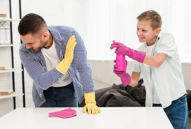 Vater und sohn spielen zusammen, während sie das haus putzen
