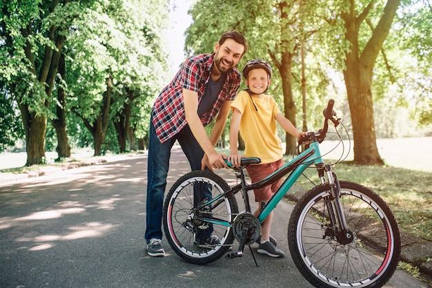 Vater und sohn stehen und halten ein fahrrad