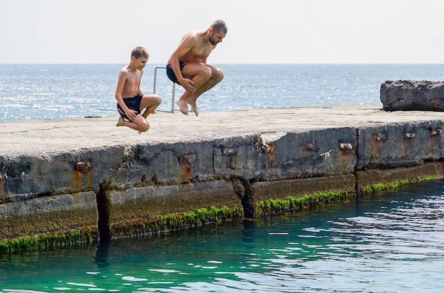 Vater und sohn tauchen vom pier ins meer.
