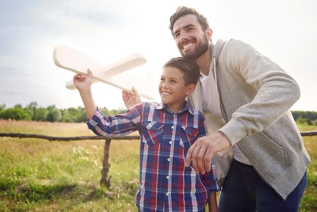 Vater und sohn testen ein papierflugzeug