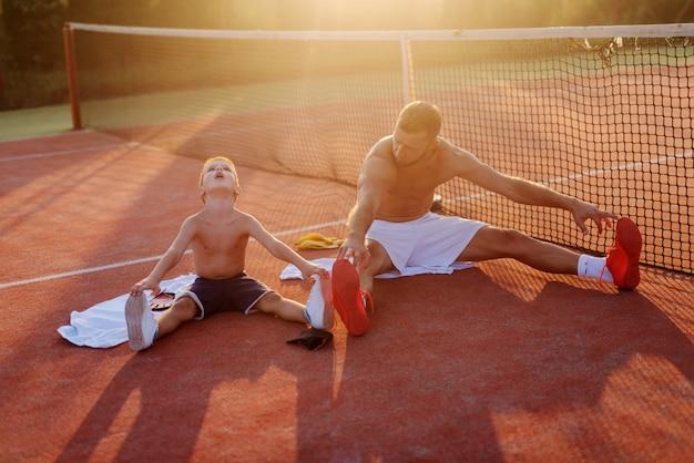 Vater und sohn trainieren zusammen. auf dem trainingsfeld sitzen und sich nach starkem regen dehnen. gemeinsam spaß haben.