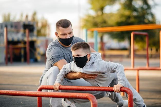 Vater und sohn treiben bei sonnenuntergang in masken sport auf dem sportplatz