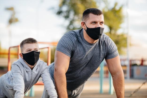 Vater und sohn treiben während des sonnenuntergangs sport auf dem sportplatz in masken. gesunde elternschaft und gesunder lebensstil.