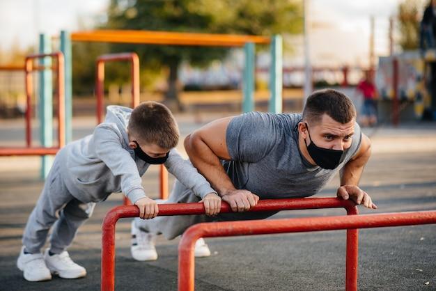 Vater und sohn treiben während des sonnenuntergangs sport auf dem sportplatz in masken.