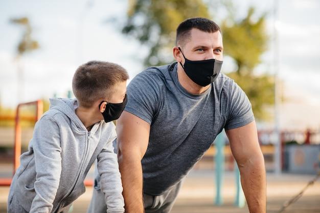 Vater und sohn treiben während des sonnenuntergangs sport auf dem sportplatz in masken