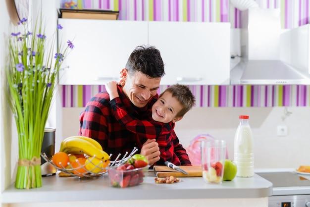 Vater und sohn umarmen sich in einer küche. sitzen am tisch voller frischer früchte.