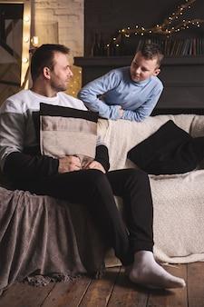 Vater und sohn unterhalten sich zu hause im wohnzimmer am weihnachtsbaum.