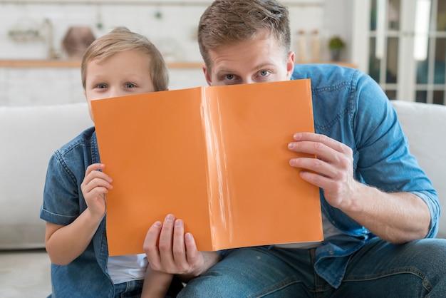 Vater und sohn verstecken sich hinter einem notizbuch