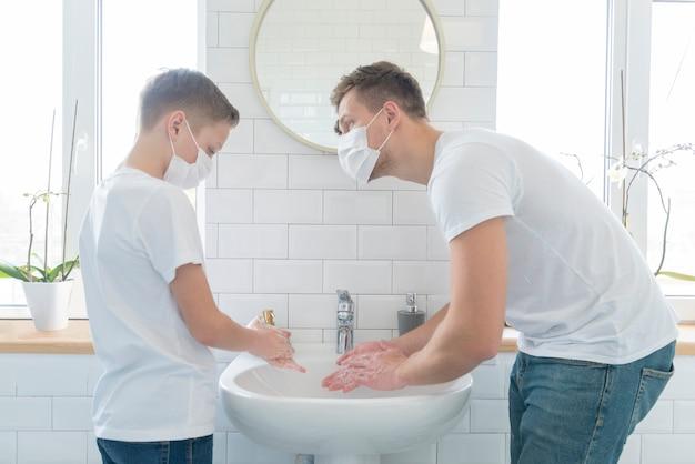 Vater und sohn waschen ihre hände mittlerer schuss