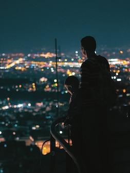 Vater und sohn, welche die nachtstadt betrachten.