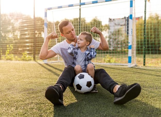 Vater und sohn zeigen muskeln auf dem fußballplatz