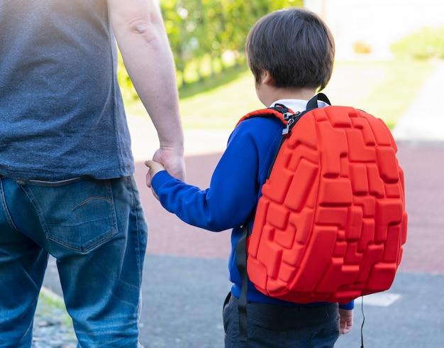 Vater- und sohnhändchenhalten zusammen, tragender rucksack des schülers, der zur schule geht