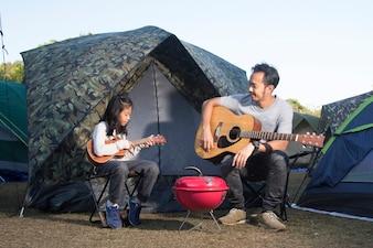 Vater und Tochter am camping spielen Ukulele und Gitarre