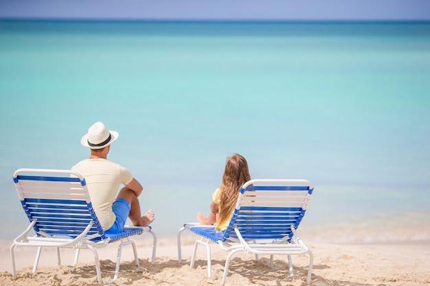 Vater und tochter am strand sitzen auf chaiselongue