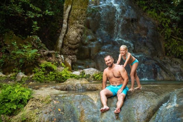 Vater und tochter an einem wasserfall im dschungel. reisen in der natur in der nähe eines wunderschönen wasserfalls, türkei