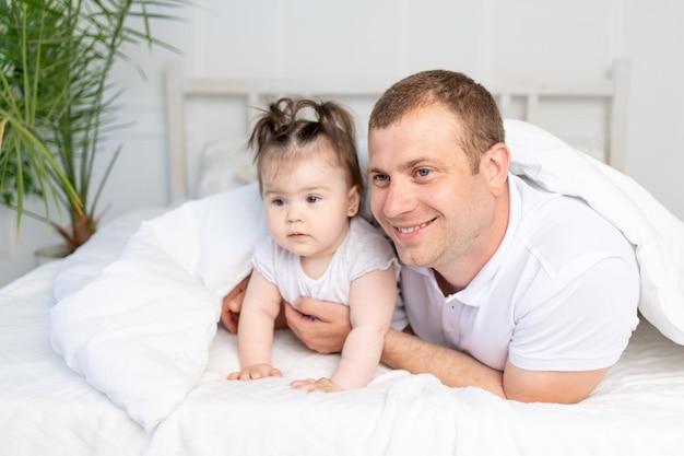Vater und tochter auf dem bett unter der decke, lächelnd und umarmt. glückliche familie
