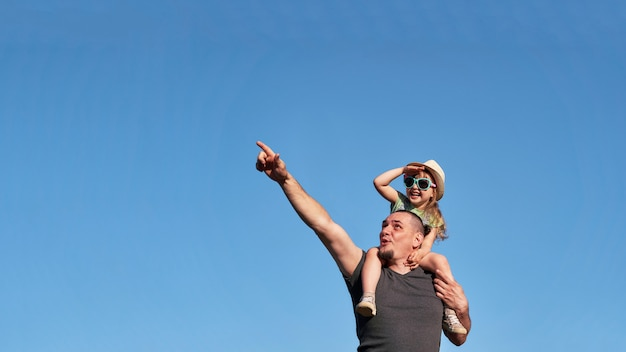 Vater und tochter auf schultern freuen sich glücklich.