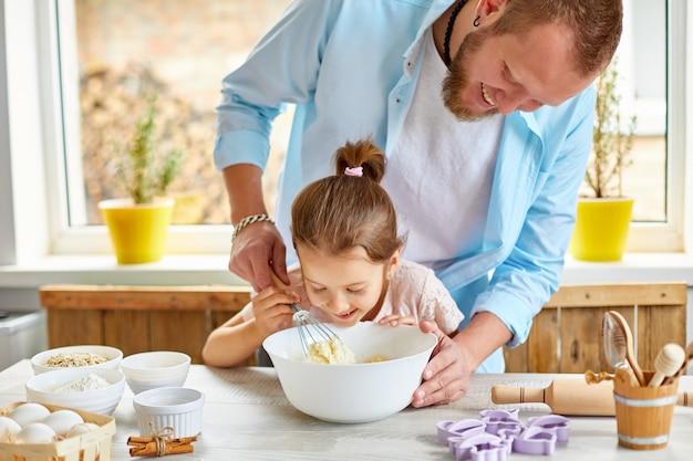Vater und tochter bereiten gemeinsam teig in der küche vor, familie kocht zu hause