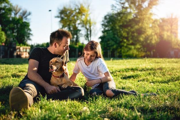 Vater und tochter, die am park mit hund sich entspannen