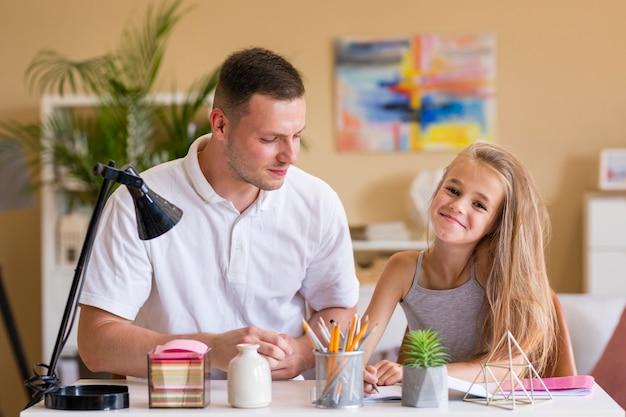 Vater und tochter, die an einem schreibtisch lächeln und sitzen