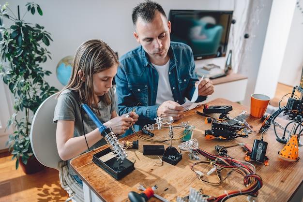 Vater und tochter, die an elektronikkomponenten arbeiten