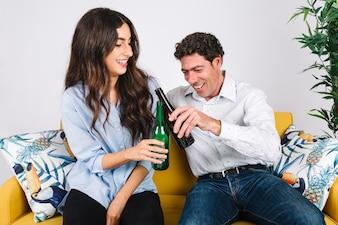 Vater und Tochter, die Bier auf Sofa trinken