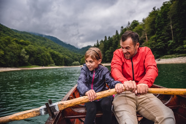 Vater und tochter, die ein boot auf dem see rudern