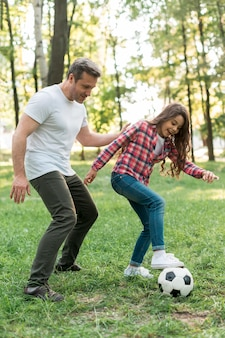 Vater und tochter, die fußball im park spielen