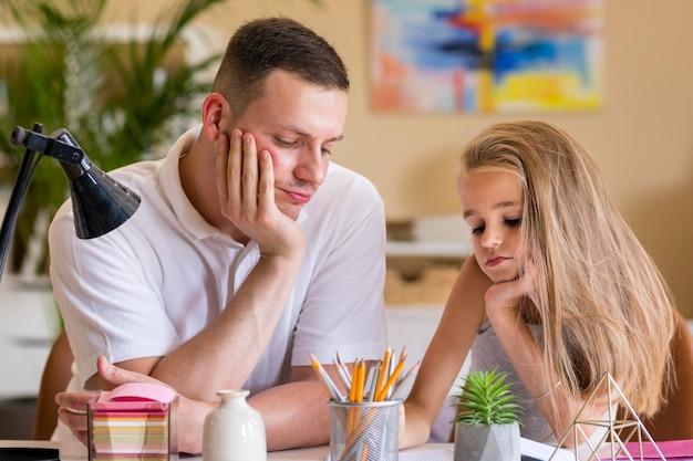 Vater und tochter, die gelangweilt sind und hausaufgaben machen