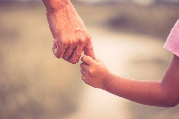Vater und tochter, die hand im weinlesefarbton zusammenhalten