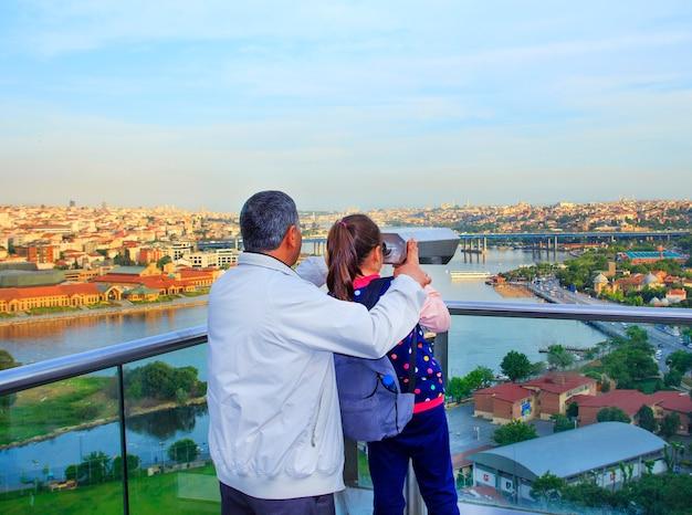 Vater und tochter, die istanbul durch ein fernglas betrachten