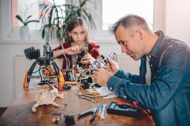 Vater und tochter, die roboter bauen
