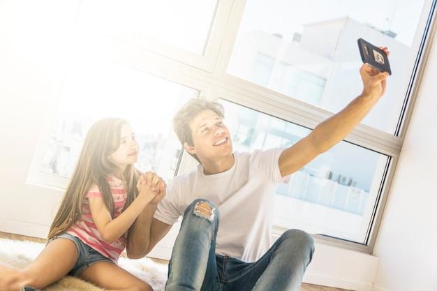 Vater und tochter, die selfie am handy durch händchenhalten nehmen