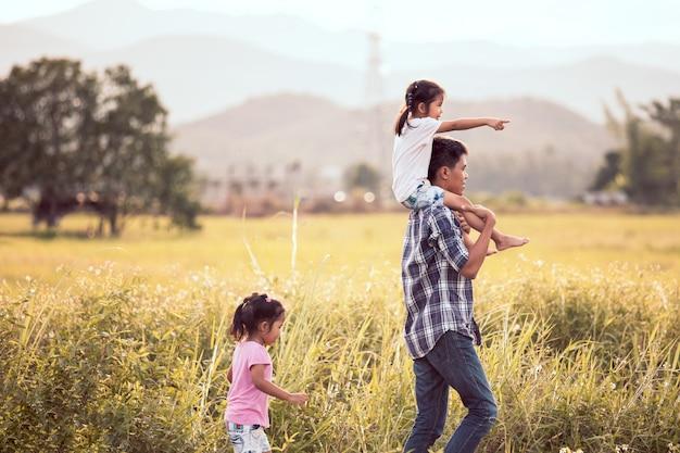Vater und tochter, die spaß haben und zusammen im getreidefeld spielen