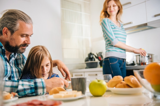Vater und tochter, die tablette in der küche verwendet