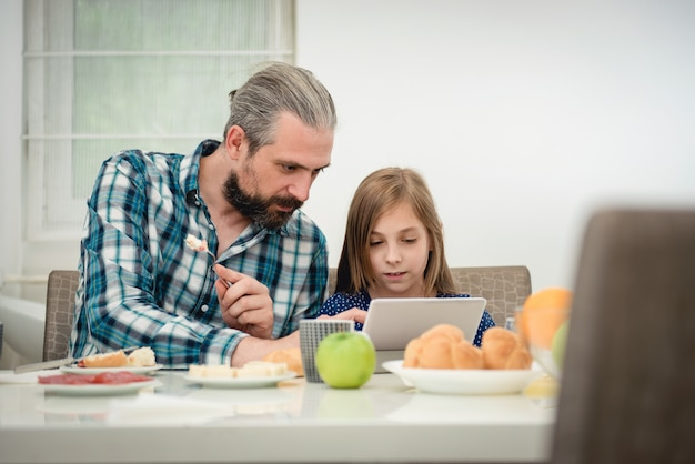 Vater und tochter, die tablette während des frühstücks verwenden