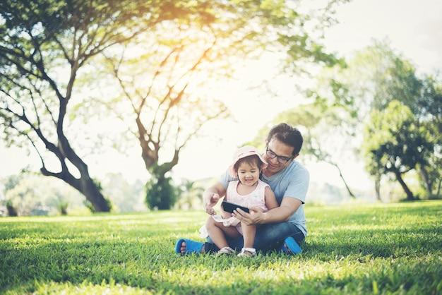 Vater und tochter, die unter verwendung des smartphone im park lächeln